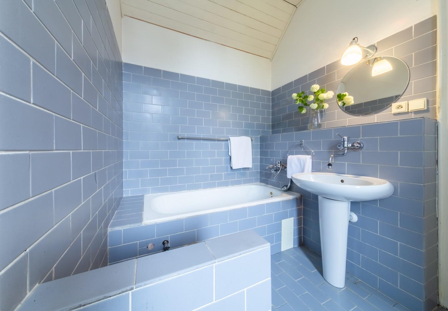 koupelna zrcadlo lampa vana umyvadlo kvetina rucnik